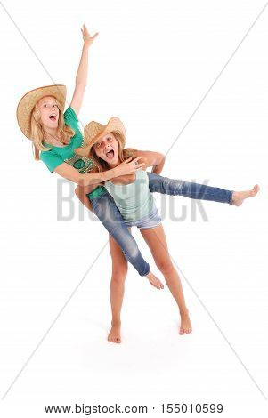 Two pretty thirteen year old girls wearing a big floppy straw sun hat isolated on white