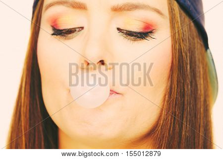 Woman casual style teen girl cap on head colorful makeup doing bubble with chewing gum closeup. Youth style