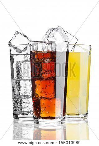Glasses of cola orange soda lemonade with ice on white background with reflection