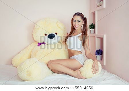 Young Beautiful girl at bed. Cheerful happy sexy woman enjoying a relaxing stay in her bed with a big toy bear.