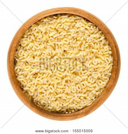 Alfabeto pasta in wooden bowl. Italian miniature noodles shaped as letters of the alphabet prepared with eggs. Uncooked dried durum wheat semolina pasta. Isolated food macro photo on white background.
