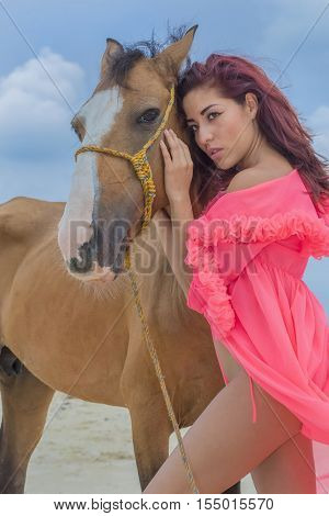 A hispanic brunette model rides a horse on a Caribbean beach