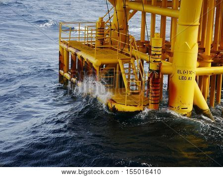 High wave hitting the Boat Landing and Producing Slots at Offshore Platform during bad weather conditions (high wave) - Oil and Gas Industry