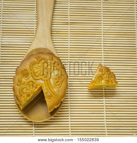 Mid-Autumn Festival moon cake in spoon on wooden traditional mat