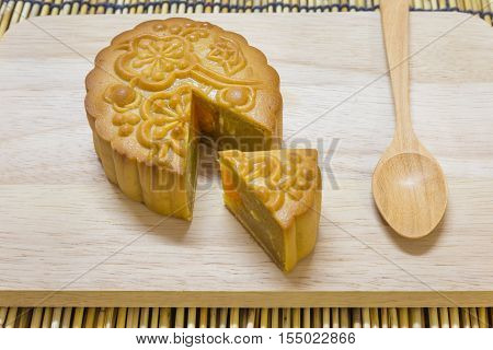 Mid-Autumn Festival moon cake on wooden table with spoon