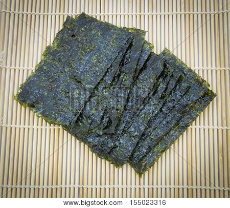 closeup roasted seaweed snack (kim nori) on traditional bamboo mat