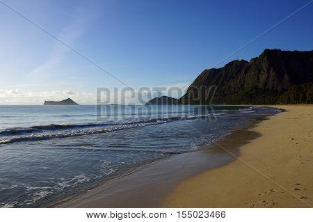 Gentle wave lap on Waimanalo Beach looking towards Rabbit island and Rock island in the early morning Oahu Hawaii. June 2016.
