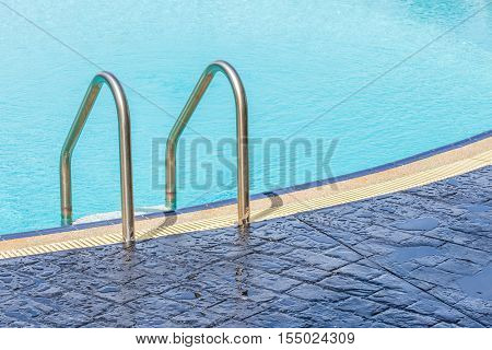 The view of metallic ladder entrance to clear blue swimming pool.