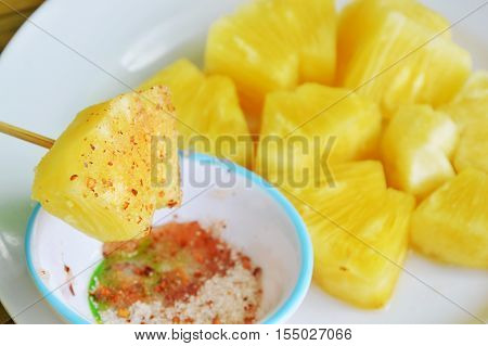 pineapple slice dipping with mixed sugar salt and pepper on wooden stick