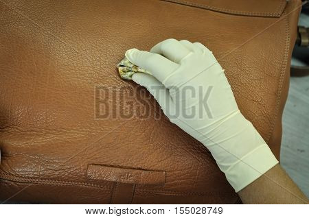 Worker Cleaning and Moisturizing a Leather Bag in Leather Factory. A leather factory worker removes stains and soil as well as to replenish vital oils and restore color.