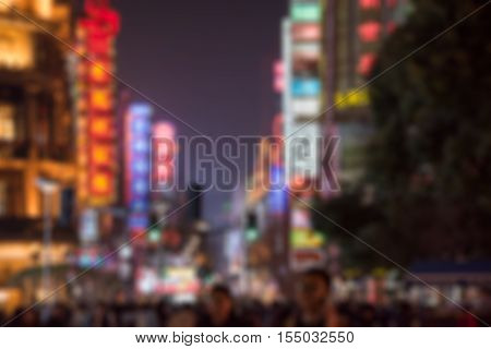 Crowd On Nanjing Road Against Illuminated modern buildings.
