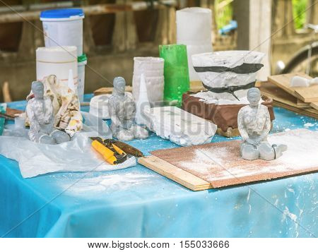 Working desk of arstist to make a female figure by pouring liquid resin in a mold