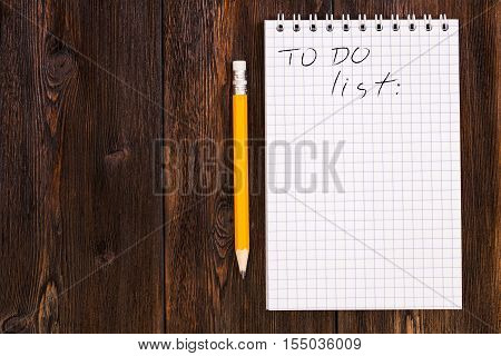 Blank notebook and pencil with todo list on a dark wooden background