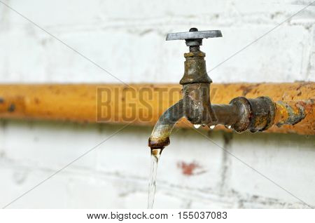 Rusty old faucet with flowing water - white wall