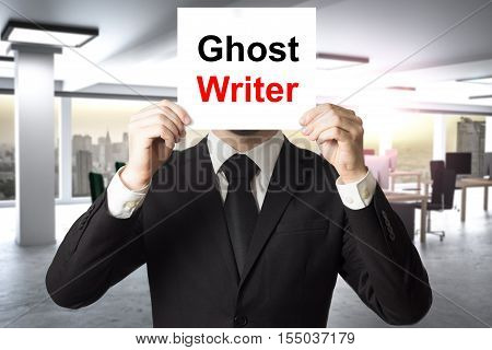 businessman in black suit hiding face behind sign ghost writer