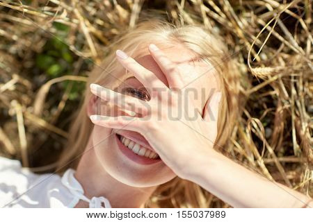 nature, summer holidays, vacation and people concept - close up of happy young woman lying on cereal field and covering face by hand