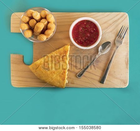 A photo of a tortilla, traditional Spanish snack, on a wooden board, with tomato sauce and bread sticks, shot from above, with copyspace