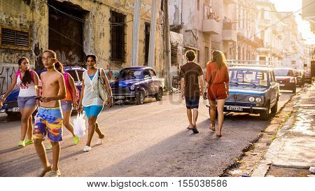 Havana, Cuba on December 22, 2015: Cuban people walking in a street in old Havana at sunset. On the side of the road there are many oldtimers.