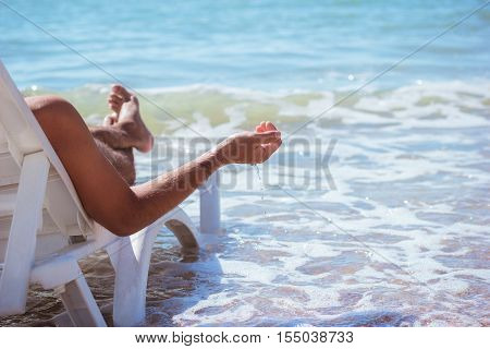 Young slender man resting lying on a lounger on the beach . Summer beach holiday