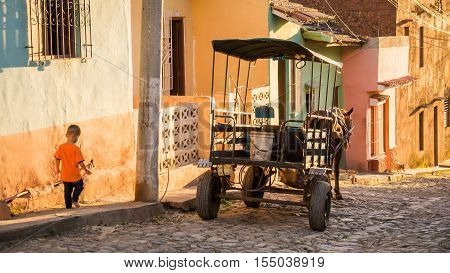 Trinidad, Cuba on December 29, 2015: In late afternoon light a horse carriage is waiting for passengers in front of colorful buildings in Trinidad. Meanwhile a young boy is walking down the sideway.