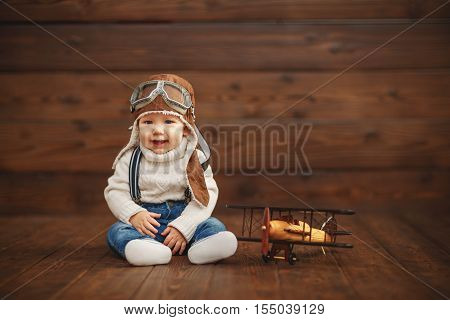 funny baby boy pilot aviator with airplane laughing on wooden background