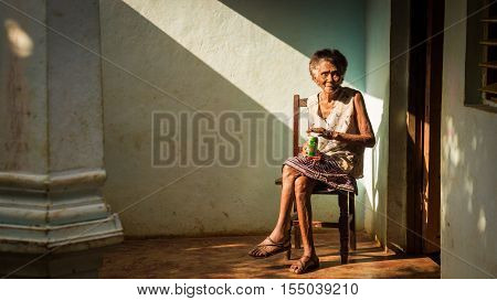 Baracoa, Cuba on January 7, 2016: In a Cuban house an old woman is enjoying a beer in the sun