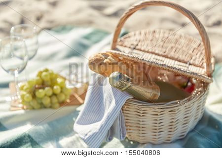 food, holidays and celebration concept  - close up of picnic basket champagne bottle and french roll bread on  summer beach