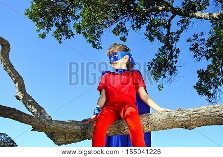 Superhero Girl Sits On A Tree
