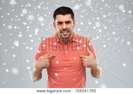 emotion, gesture, winter, christmas and people concept - arguing angry man pointing finger to himself over snow on gray background