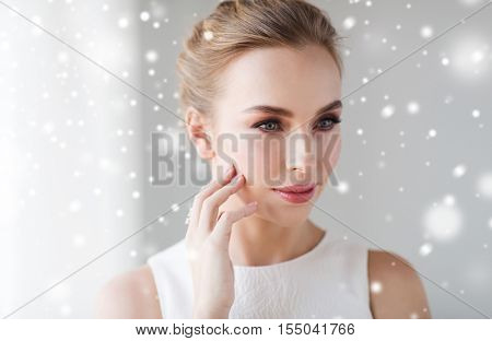 beauty, christmas, holidays and people concept - close up of beautiful smiling woman in white dress touching her face over snow