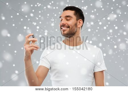 perfumery, beauty, winter, christmas and people concept - happy smiling young man with male perfume over snow on gray background