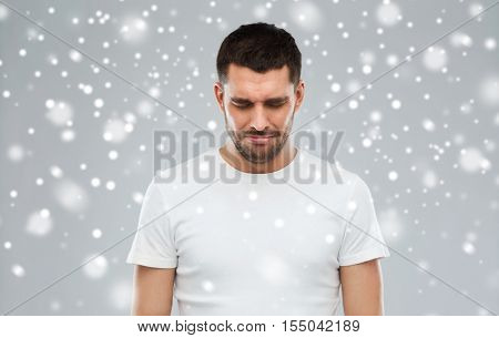 emotion, sadness, winter, christmas and people concept - unhappy young man over snow on gray background