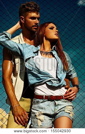 High fashion look.glamor closeup portrait of beautiful couple sexy stylish blond young woman model with bright makeup with perfect sunbathed skin and handsome muscled man in vogue style in jeans outdoors behind blue sky