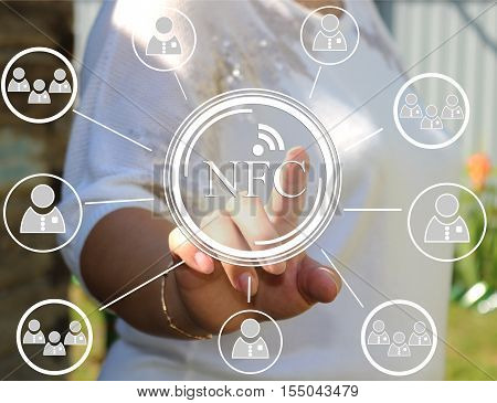 A young woman presses the NFC icon on the touch screen. NFC near field communication, network. Web icons.The latest technology is out of town , in nature.