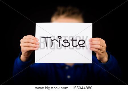 Studio shot of child holding a sign with Spanish word Triste - Sorry