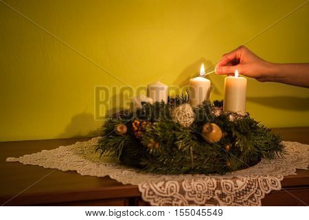 Female hand fire candles on the Advent wreath