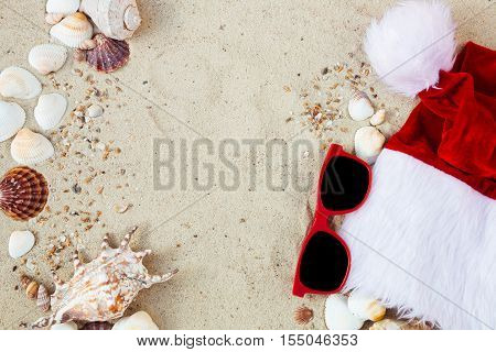 Christmas hat and red sunglasses on the beach. Santa hat and eyeglasses on the sand near shells. Holiday. New year vacation. Copy space. Frame. Top view.