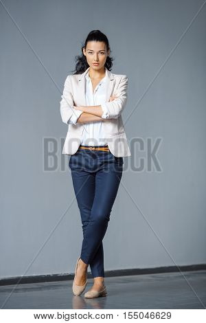 Beautiful brunette business woman in suit posing outdoors against gray background and looking at camera in full lenght. Copy space