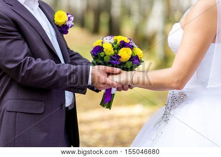 Happy bride and groom holding hands. Newlyweds are in the park and hold hands. Bride in a beautiful wedding dress holding a wedding bouquet and groom's hands.