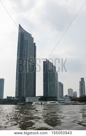 BANGKOK THAILAND - JANUARY 25 2015: Skyscrapers along Chao Phraya River in Bangkok. Chao Phraya river is a major river in Thailand