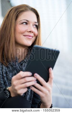 Young Woman Smiling With Tablet In Hands