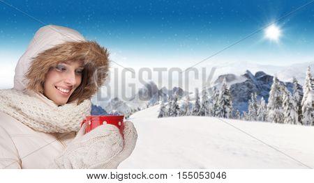 Beautiful winter portrait of young brunette woman drinking tea in the winter snowy scenery