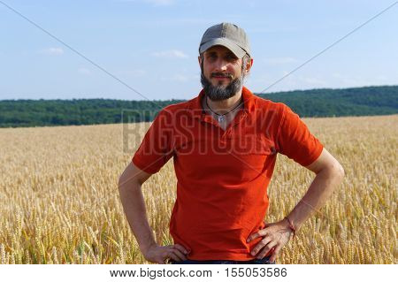 a bearded man in a cup standing in a wheat field