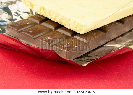 Stick Of White And Dark Dessert Chocolate On A Red Background