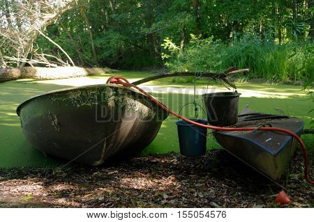 Old canoe and a wooden boat ashore the pond is almost sunk