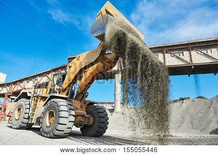 Mining industry. heavy wheel loader loading granite rock or ore at crushing and sorting plant poster