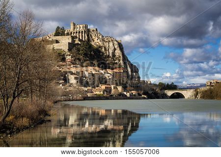 Citadel of Sisteron and Durance River in hiver with clouds in afternoon light. Sisteron and its fortifications is located in the Southern Alps (Alpes de Haute Provence). France