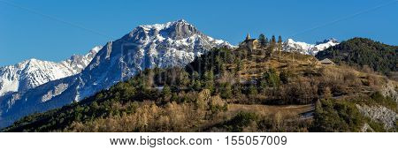 Winter panoramic view of Montgardin village church with the Pic Morgon (Grand Morgon) in the background. Winter in the Southern French Alps (Hautes Alpes). France