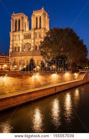 Notre Dame de Paris cathedral illuminated at twilight with the Seine River on Ile de La Cite. Summer evening in the 4th Arrondissement, Paris, France