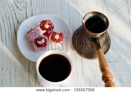 Top view of a coffee Turkish delight and pots in the sun on a white wooden background
